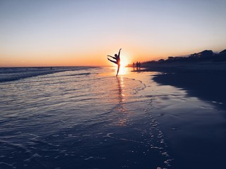 Silhouette ballet dancers dancing on the beach during sunset