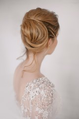 Rear view of bride in bun standing against white background