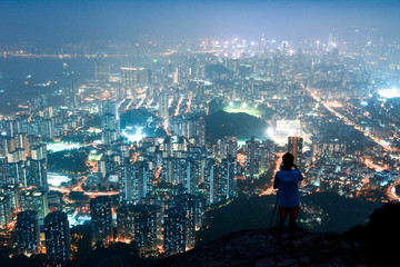 Rear view of a man taking picture of a city at night