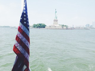 Close up of American flag with statue of liberty in the background