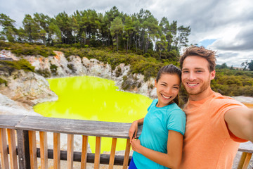 New Zealand tourist attraction couple tourists taking selfie travel destination, Waiotapu. Active geothermal green pond, Rotorua, north island.