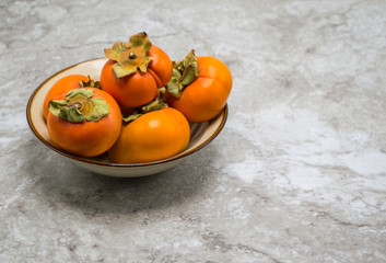 ripe orange persimmons stacked in a bowl on a gray marble counter top with copy space