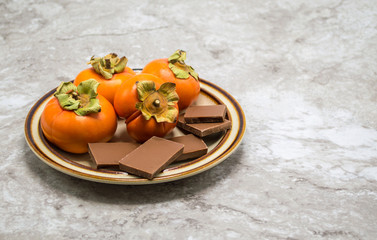 small plate with ripe orange persimmons and pieces of chocolate on a gray marble counter top with copy space