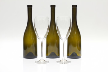 Three empty upturned wine bottles and two glasses on a white background