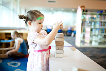 Cute little girl playing with blocks at the library
