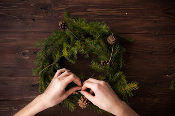 Close up of woman's hand making Christmas wreath on wooden table