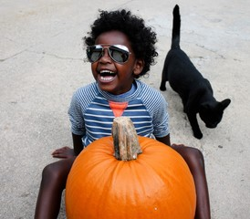 Smiling boy with pumpkin while sitting on street
