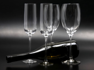 four empty wine glasses and a reclining wine bottle