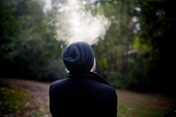 Rear view of man exhaling smoke while standing in forest