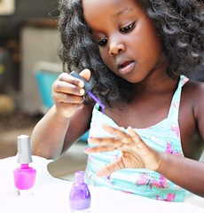 Close up of girl applying nail polish on fingers