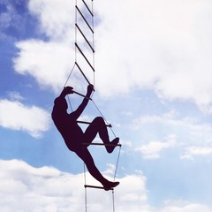 Silhouette of a man climbing a rope ladder in the sky