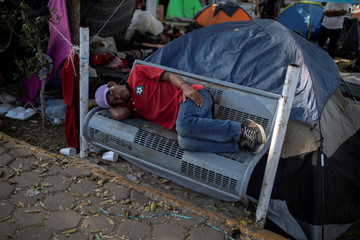 A migrant, part of a caravan of thousands from Central America trying to reach the United States, sleeps on a bench at a temporary shelter in Tijuana