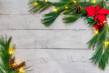 White Christmas Background with spruce greens, ornaments and lights