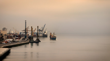 The port of Lisbon on a foggy day with their containers cranes, Portugal.