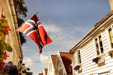 The flag of Norway on a wooden wall of a house outdoors in Stavanger.