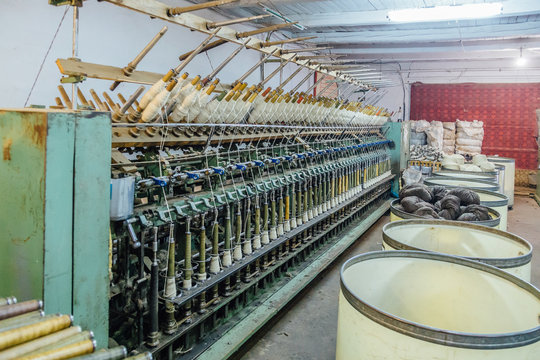 Spinning production line. Spinning machinery with spindles and wool yarns