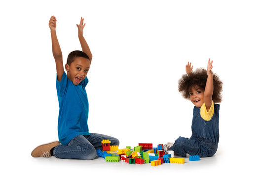Little african excited kids playing with lots of colorful plastic blocks indoor. Isolated