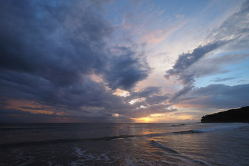 Sunset over the beach of Playa El Coco, Nicaragua, with a colorful cloudscape reflected in the coastal water.