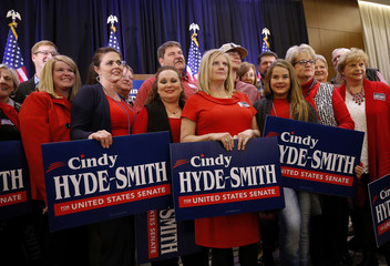 Supporters of Republican U.S. Senator Cindy Hyde-Smith pose for a photo during an election night party in Jackson