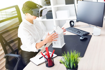 Young girl sitting in virtual reality glasses. Before her on the table is the layout of the house.