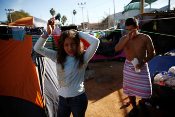 Jamie Mejia Meza combs her hair in front of her family's tent at a temporary shelter in Tijuana
