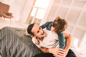 Energetic kid play-wrestling with his dad on the bed.