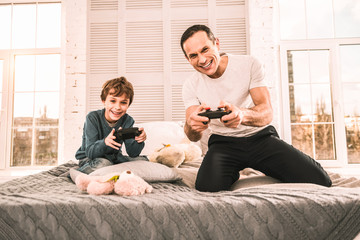 Little boy enjoying a crazy evening playing games with his dad.