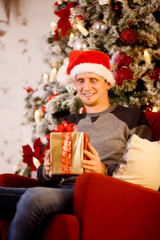 Photo of happy man in Santa hat with gift in his hands