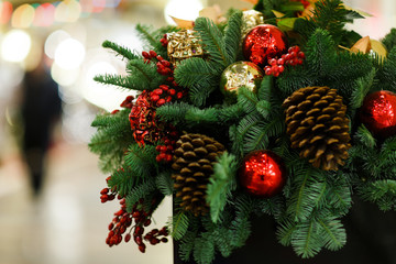 Image of decorated Christmas spruce with cones and red balls in store .