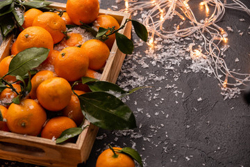 Image of tangerines in wooden box with burning garland