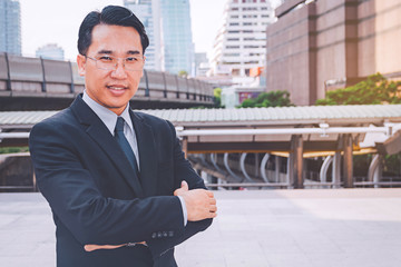 Portrait of a young successful businessman standing in city