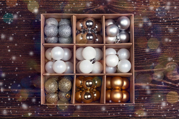 Box with a set of Christmas balls on a wooden table.