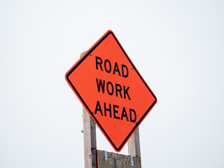 Road work ahead orange sign posted on wooden post on overcast sky