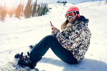 Woman snowboarder relaxing after snowboarding, taking photos of winter nature in the mountains using smart phone in the morning copyspace connectivity mobility carrier lifestyle technology