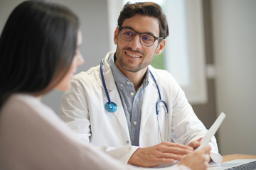 Modern young doctor speaking to patient in office