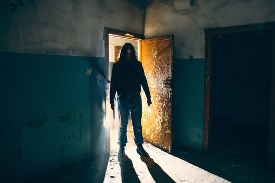 Silhouette of criminal or maniac with knife in hand in old scary building, serial killer with cold weapon