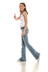 happy young pretty woman wakling in bell bottom jeans on white background and showing thumbs up
