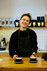 Vertical portrait of Friendly female barista with a two cups of coffee on counter at the local coffee shop smiling to the customer cheerfully. Modern coffee shop interior.