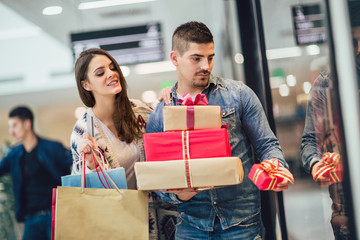Young couple doing Christmas shopping in the shopping mall