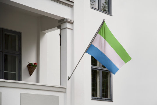 Sierra Leone flag hanging on a pole in front of the house. National flag waving on a home displaying on a pole on a front door of a building and raised at a full staff.