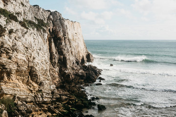 Beautiful view of the Atlantic Ocean and coastal cliffs off the coast of Portugal on a sunny day.