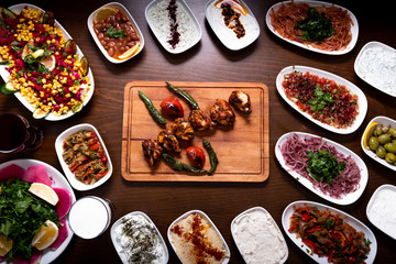 Grilled bbq chicken shish kebab on wooden plate with salads and mezes