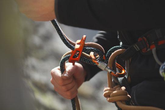 Easy belay-descender device in the hands of a climber closeup. Climbing gear and equipment.  Tilt-Shift effect.