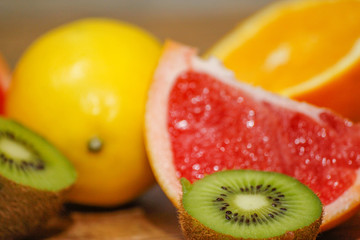 Various raw citrus fruit on wooden table. Close-up of lemon, orange, grapefruit and kiwi.