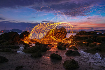 reflection of spark fire swirl from steel wool with long exposure speed motion abstract at sunrise in the sea.