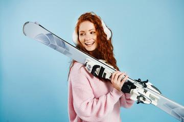 Smiling girl holding her skis