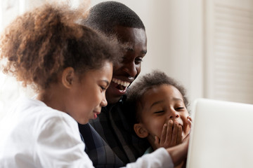 Happy African American family using laptop, computer together, father with daughter and preschooler son make video call, watching funny video, cartoons, sitting on couch at sitting room, close up