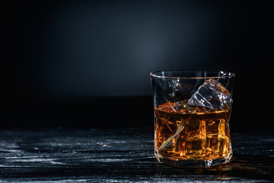 Glass of whisky with ice on wooden table against dark background