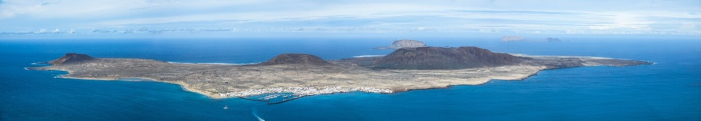 Caleta del Sebo, remote volcano island seen from a viewpoint on the north of Lanzarote, Canary Islands. Panorama background.