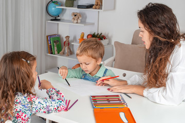 Small children with a nanny or with a young mother or with a teacher are sitting at the table in the room and drawing with colored pencils
